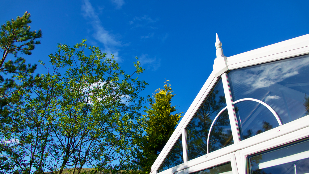 Top of a white conservatory on a blue sky